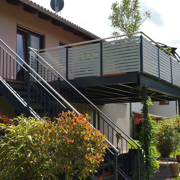 Eine Treppe führt an einem Haus auf den Balkon