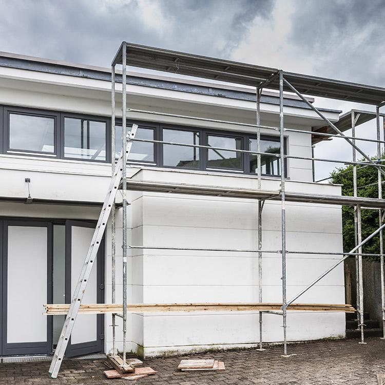 Ein Baugerüst vor einem weißen Haus
