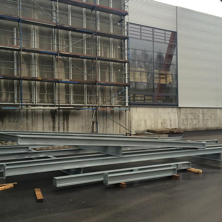 Metallträger liegen vor einem Gebäude auf dem Boden.