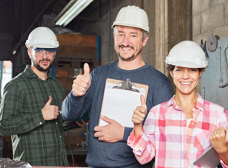 Drei Arbeiter geben einen Daumen nach oben in einer Werkstatt.
