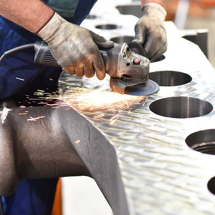 Ein Mann arbeitet mit einem Schleifgerät an einem Metallstück